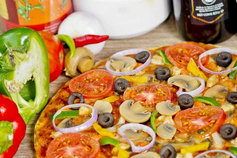 Popular colorful ingredients as like tomatoes, cheese, mushroom, capsicum, olives and other ingredients baked healthy Pizza.  royalty free stock photos