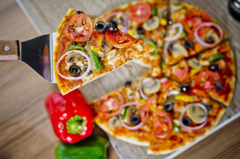 Popular colorful ingredients as like tomatoes, cheese, mushroom, capsicum, olives and other ingredients baked healthy Pizza.  royalty free stock photography
