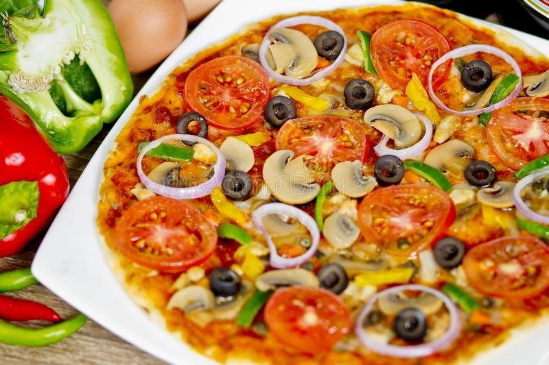 Popular colorful ingredients as like tomatoes, cheese, mushroom, capsicum, olives and other ingredients baked healthy Pizza.  royalty free stock image