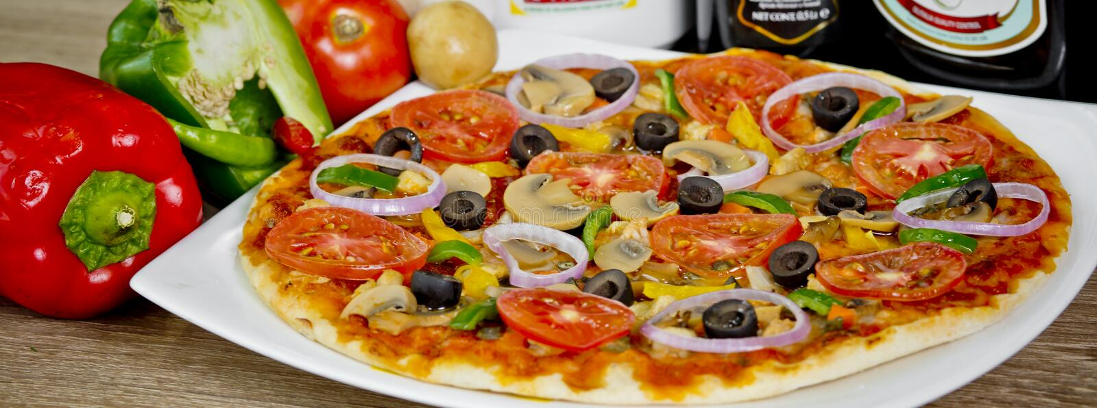 Popular colorful ingredients as like tomatoes, cheese, mushroom, capsicum, olives and other ingredients baked healthy Pizza.  royalty free stock photo