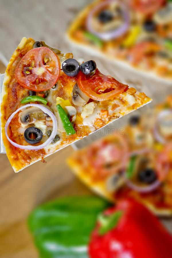 Popular colorful ingredients as like tomatoes, cheese, mushroom, capsicum, olives and other ingredients baked healthy Pizza.  royalty free stock images