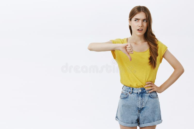 Popular girl dislikes lame try of guy. Bothered displeased and unimpressed arrogant good-looking stylish woman in yellow. T-shirt turning eyes left frowning stock image