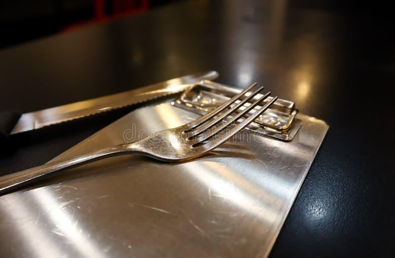 Popular inoxidável e a faca puseram sobre a bandeja de prata da conta na tabela preta imagem de stock