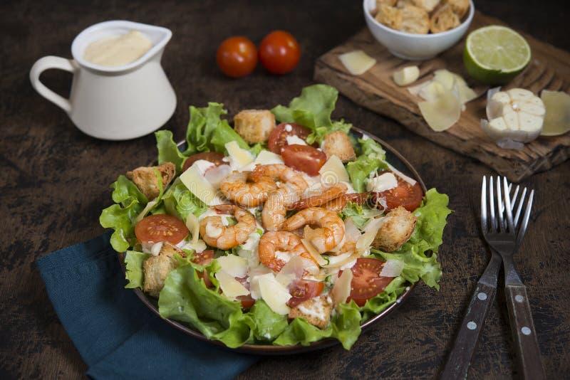 Popular Italian Caesar salad with prawns on a dark table. royalty free stock photos