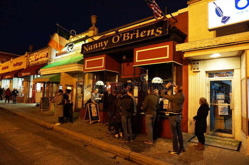 Popular Neighborhood Bar. Photo of irish pub called nanny obriens on saint patricks day on 3/17/17 at night. Here people are waiting to get inside as customers stock images