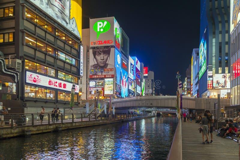 Popular night shopping scene in Osaka City at Dotonbori Namba area with illuminated neon signs and billboards along the river. Osaka, Japan - April 2016: Tourist stock photography