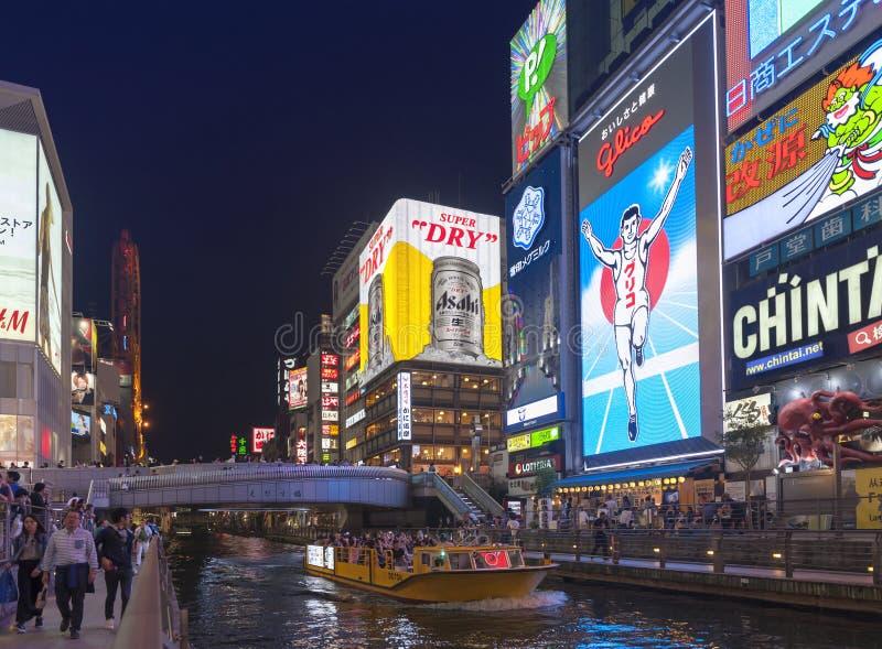 Popular night shopping scene in Osaka City at Dotonbori Namba area with illuminated neon signs and billboards along the river. Osaka, Japan - April 2016: Tourist stock image