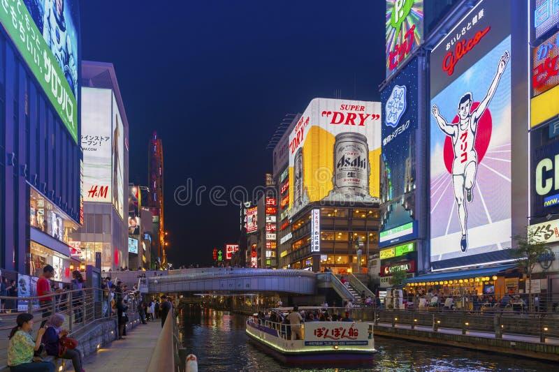 Popular night shopping scene in Osaka City at Dotonbori Namba area with illuminated neon signs and billboards along the river. Osaka, Japan - April 2016: Tourist royalty free stock image