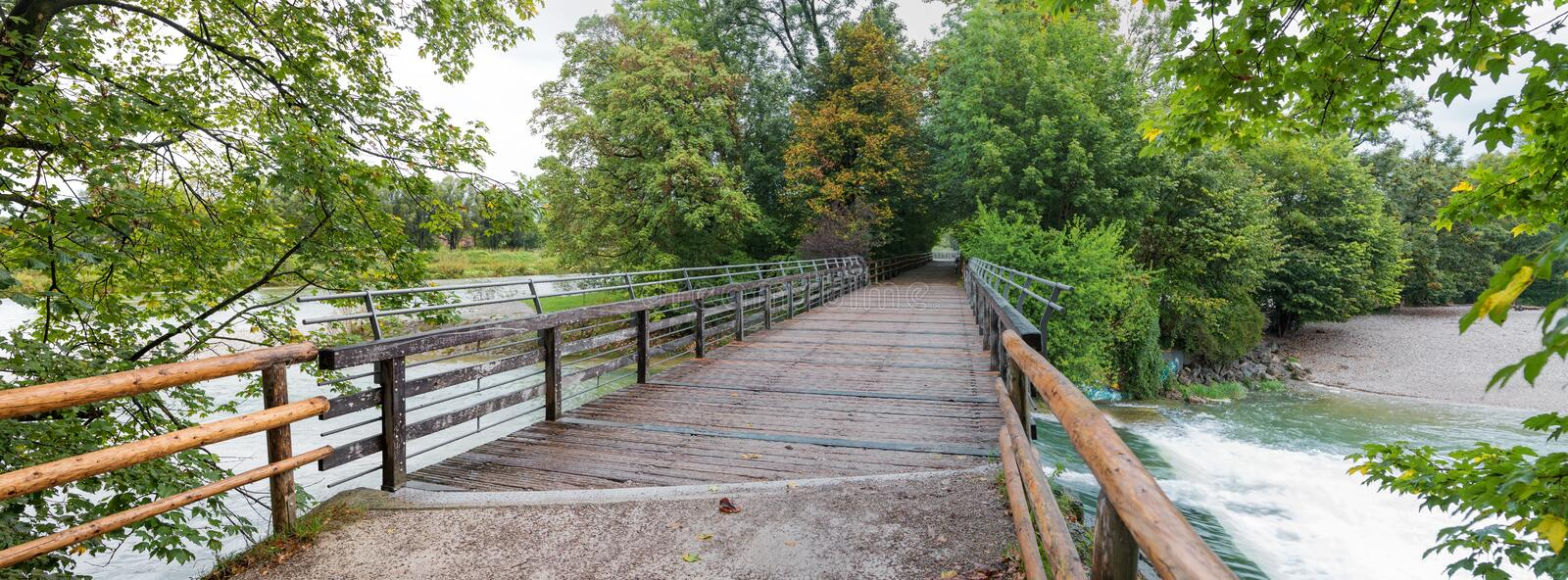 Recreational area at munich, bridge over isar river with green branches stock image