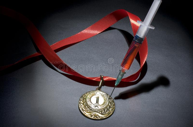 Doping in sport concept. Drugs and medals on black background. Popular red steroid in syringe as a doping stabs a gold medal on a dark background royalty free stock photography