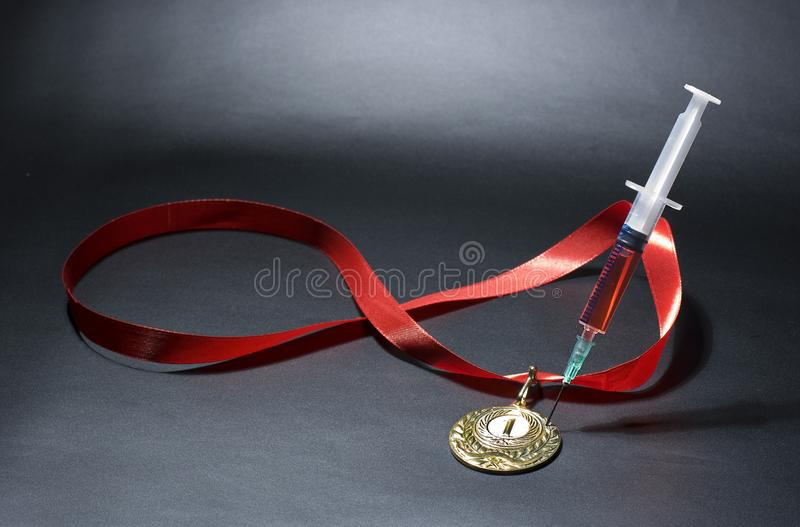 Doping in sport concept. Drugs and medals on black background. Popular red steroid in syringe as a doping stabs a gold medal on a dark background royalty free stock photo