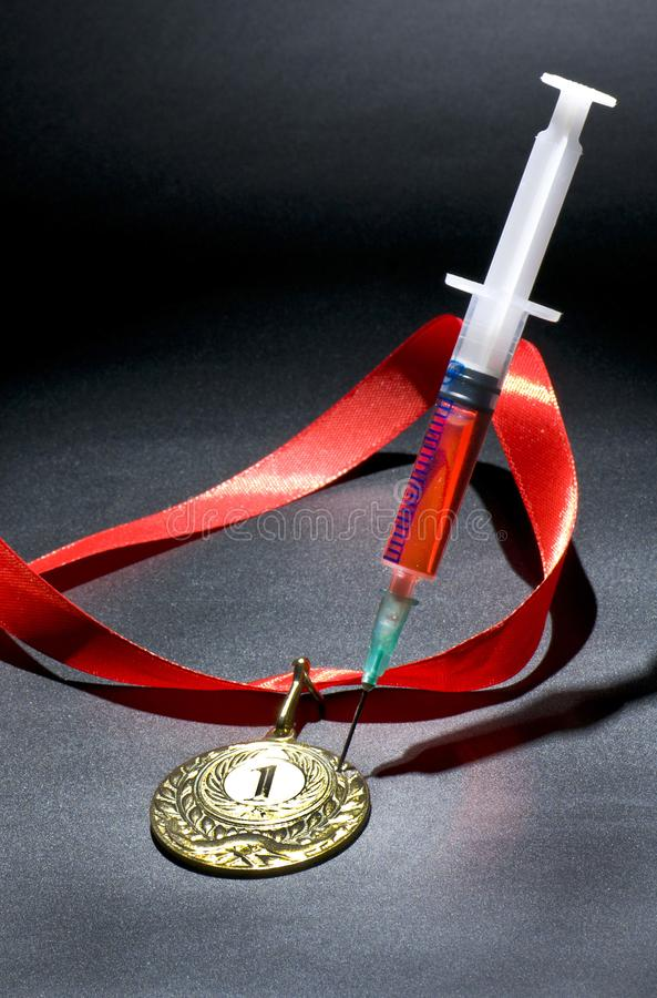 Popular red steroid in syringe as a doping stabs a gold medal on a dark background. Popular red steroid in syringe as a doping stabs a gold medal with red stripe royalty free stock photo