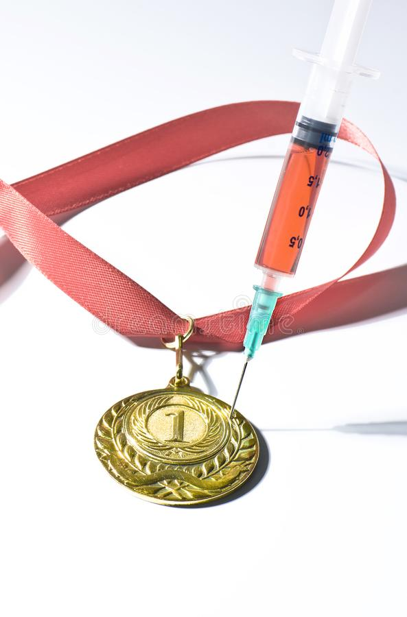 Popular red steroid in syringe as a doping stabs a gold medal on a white background. Popular red steroid in syringe as a doping stabs a gold medal with red royalty free stock images