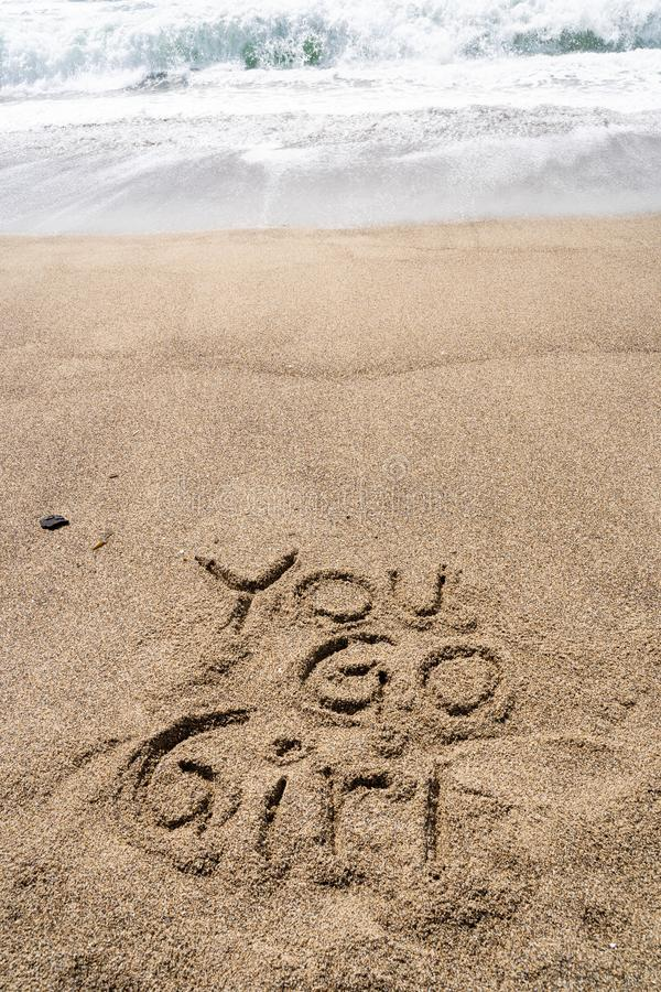 Popular 90s slang phrase You Go Girl written in sand on the beach. Nostalgia concept royalty free stock image