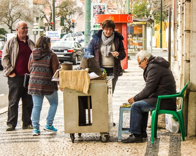 Popular seller of roasted chestnuts and customers, Lisbon, Portugal royalty free stock photo