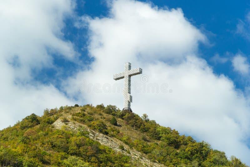 Popular sight of the Gelendzhik resort city. Worship cross on hill of Caucasian mountain against blue cloudy sky. Popular sight of the Gelendzhik resort city stock images
