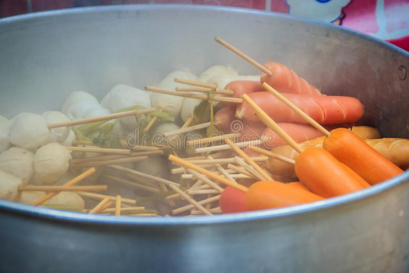 Popular street food meat ball, pork ball, fish ball and sausage with bamboo sticks in steaming pot for sale on the stall at the fr stock photos