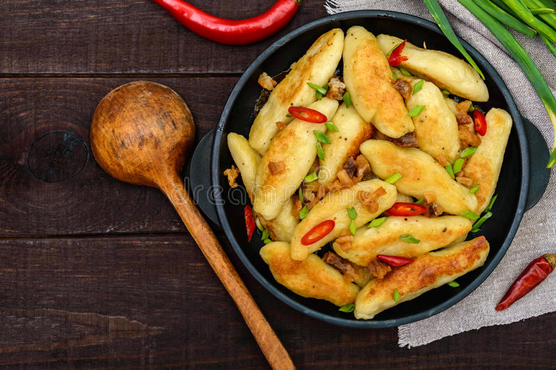 Popular traditional Czech, Hungarian, German dish: potato knedli dumplings. With slices of fried bacon, spicy red pepper and green onions. Serving on a cast stock image