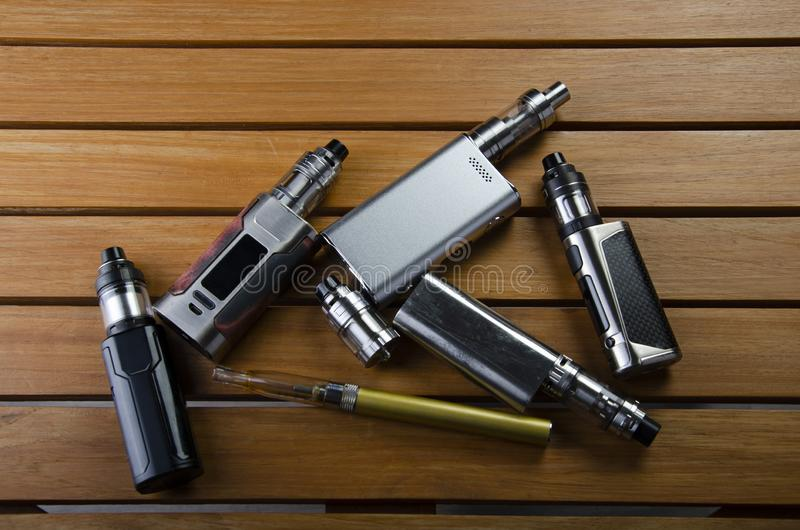 Electronic cigarette mods for ecig over a wooden background. vape devices and cigarette royalty free stock images