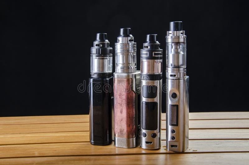 Electronic cigarette mods for ecig over a wooden background. vape devices and cigarette stock image
