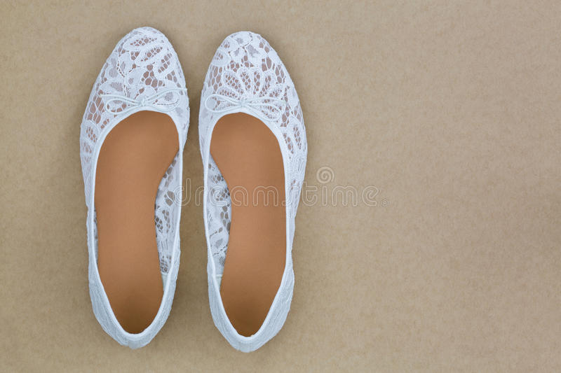 Popular white floral lace ballet flat slip on shoes on brown bac. Top view of popular white floral lace ballet flat slip on shoes on brown background royalty free stock photo