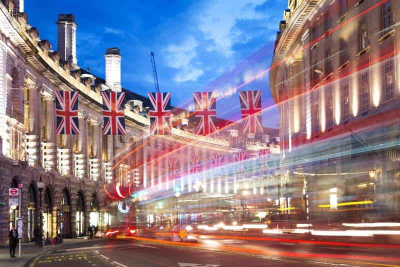 Popularna turystyczna Regent ulica z flaga zrzeszeniową dźwigarką przy nocą fotografia stock