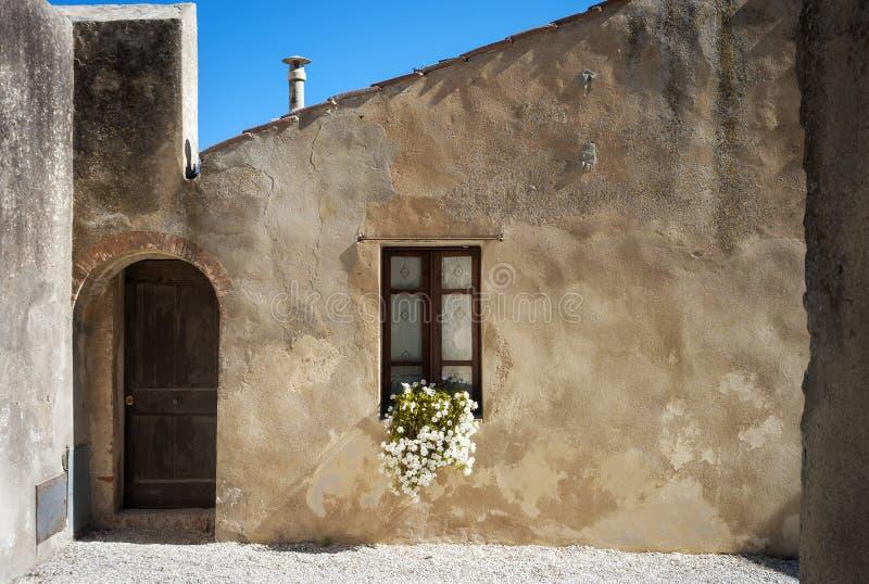 Populonia & x28; Livorno Tuscany& x29; , typisk hus moder två för färgdotterbild royaltyfri bild