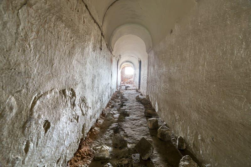Porão da construção velha da fortaleza, corredor estreito longo com teto emplastrado arcado e assoalho sujo fotografia de stock
