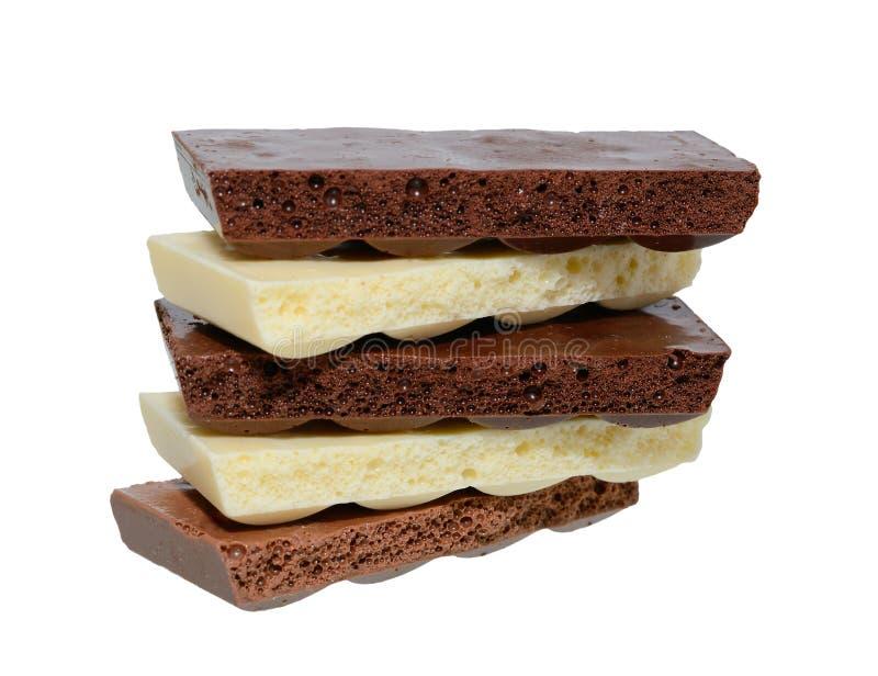 Poröse Schwarzweiss-Schokolade auf weißem Hintergrund lizenzfreie stockfotografie