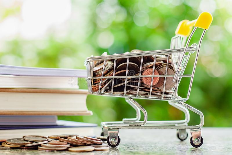 Por completo de la moneda del dinero en mini carro de la compra o carretilla con la pila o imágenes de archivo libres de regalías