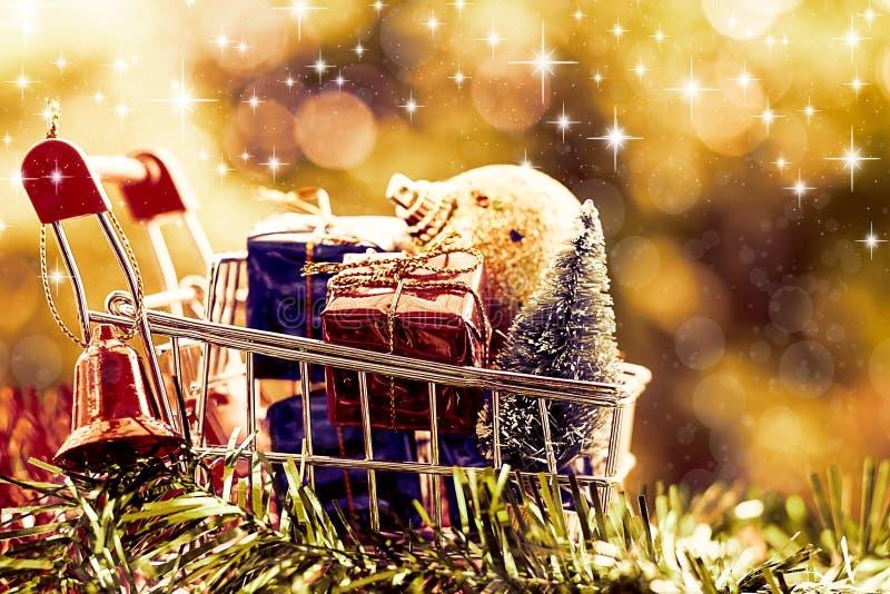 Por completo de los artículos decorativos de Navidad en el mini carro de la compra o carretilla a foto de archivo