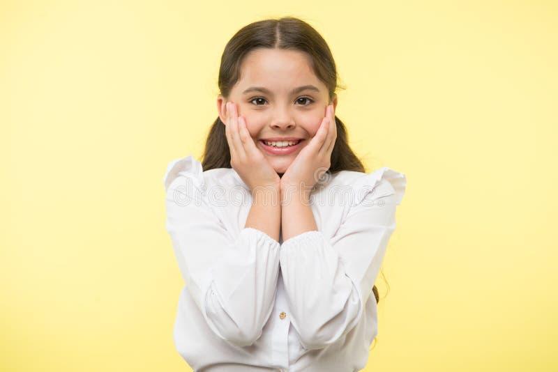 Por completo del entusiasmo La cara sonriente feliz de la muchacha toca su fondo amarillo de las mejillas La colegiala no puede e imagen de archivo libre de regalías