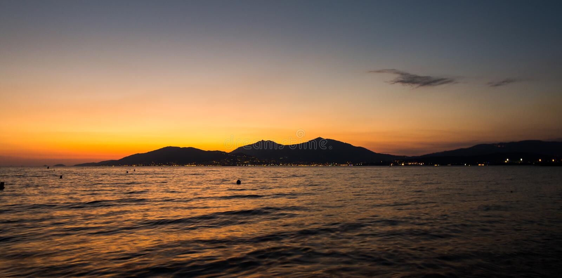 Por do sol acima da cidade pequena perto do mar Cores vermelhas e alaranjadas com o mar da água no primeiro plano Cenário românti fotos de stock