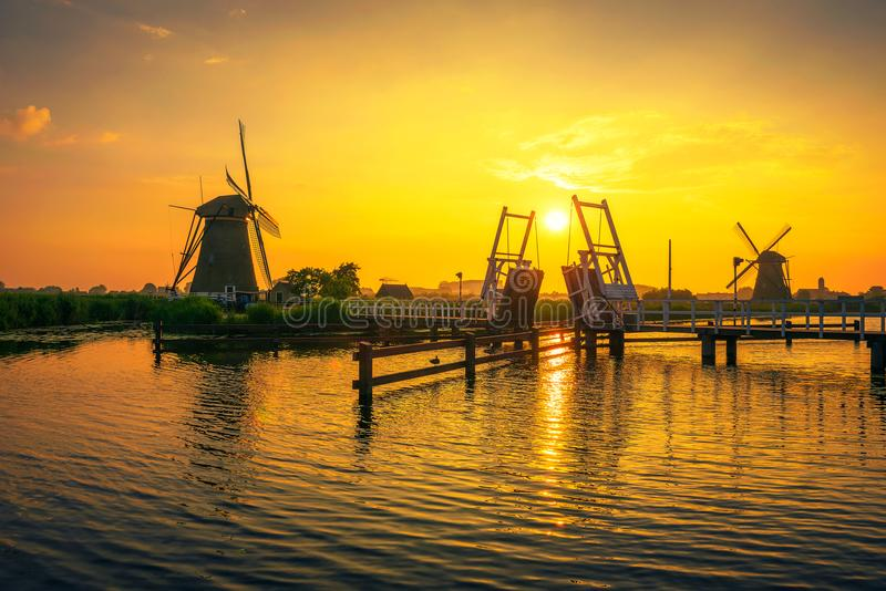 Por do sol acima de uma ponte levadiça histórica e de uns moinhos de vento velhos em Kinderdijk, Países Baixos foto de stock royalty free