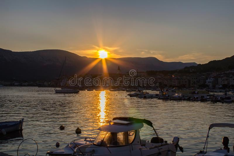 Por do sol agradável no mar com navios, Croácia de Krk da ilha de Baska fotografia de stock
