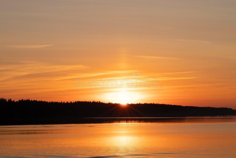 Por do sol alaranjado com Ray Of Sun Behind Forest sobre o rio imagens de stock royalty free