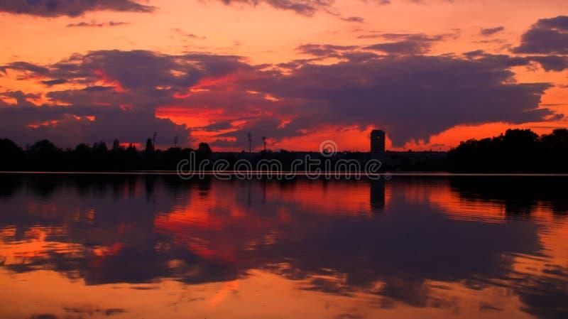 Por do sol alaranjado de surpresa sobre o horizonte com uma silhueta da torre fotografia de stock royalty free