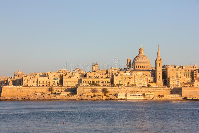 Por do sol alaranjado sobre o porto grande de Valletta foto de stock