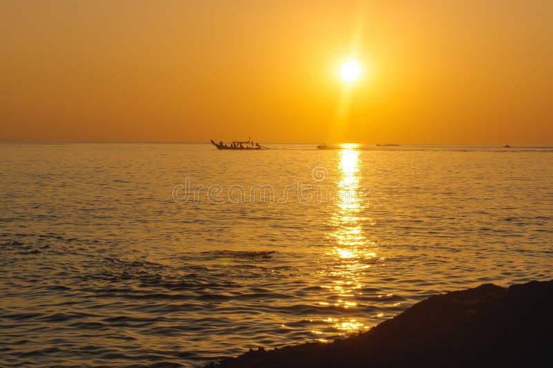 Por do sol alaranjado tropical surpreendente sobre a água, com as silhuetas da rocha na ilha de Phuket, Tailândia, imagens de stock royalty free