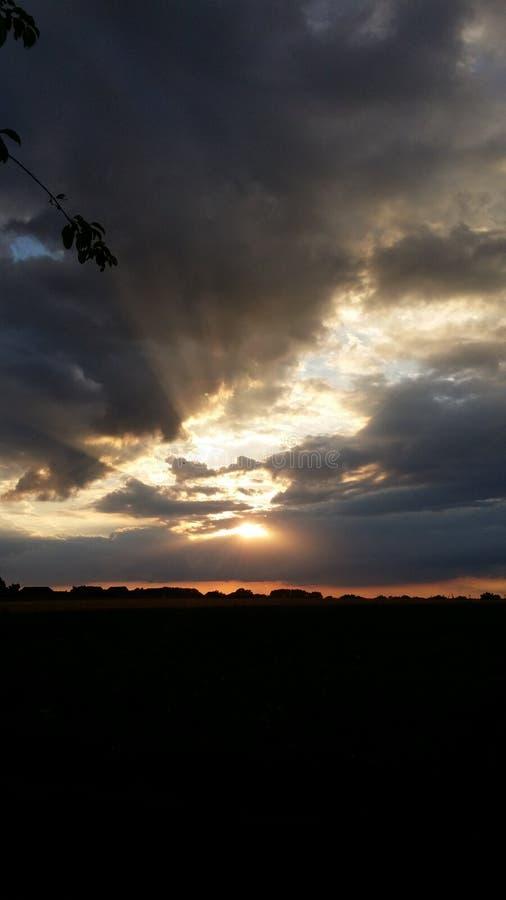 Por do sol amarelo bonito com nuvens escuras imagens de stock