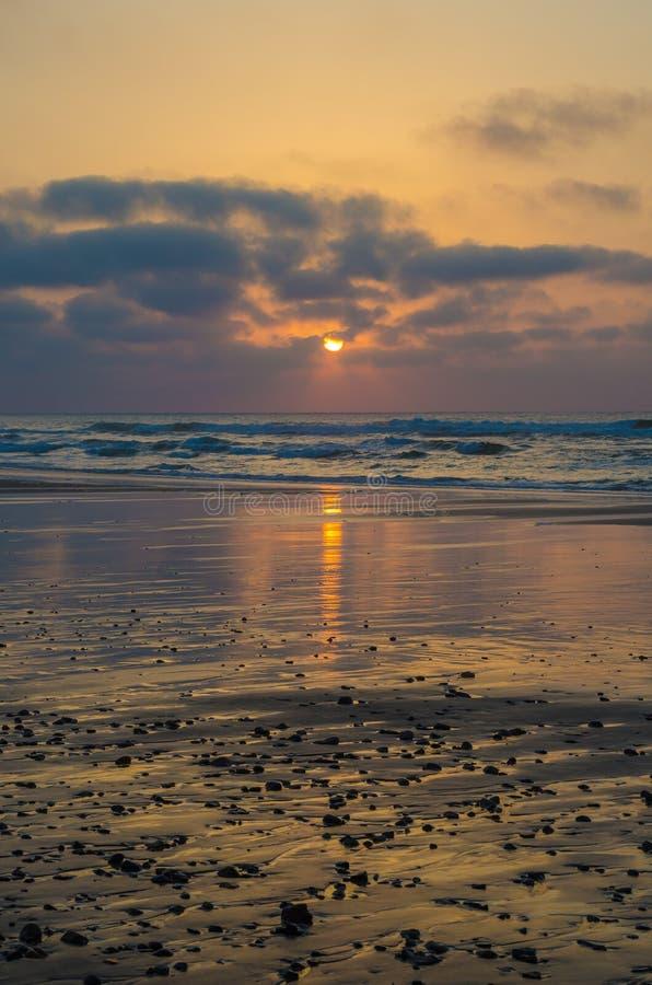 Por do sol atmosférico bonito na praia com reflexões e seixos do plack, costa em Sidi Ifni, Marrocos, Norte de África imagem de stock