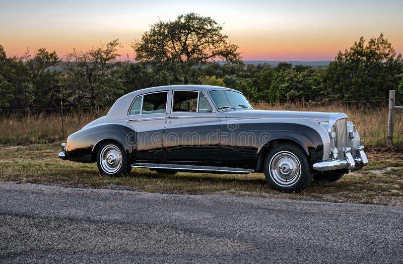 Por do sol atrás da limusina do luxery do vintage em uma estrada secundária de Texas fotografia de stock