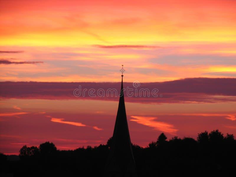 Por do sol atrás da torre de igreja fotografia de stock royalty free
