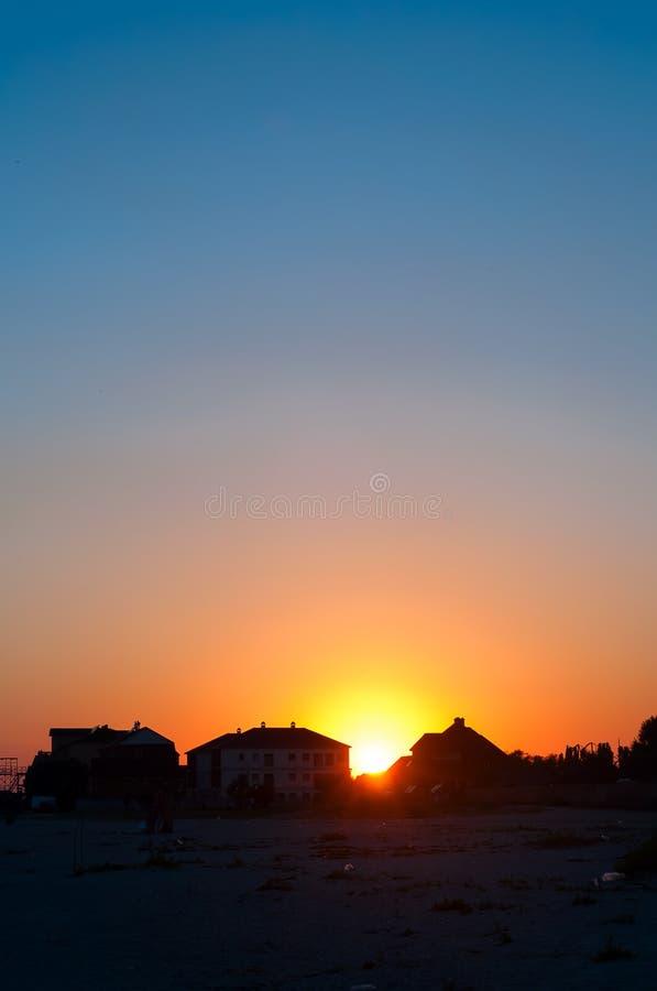 Por do sol atrás das casas e das nuvens fotos de stock royalty free