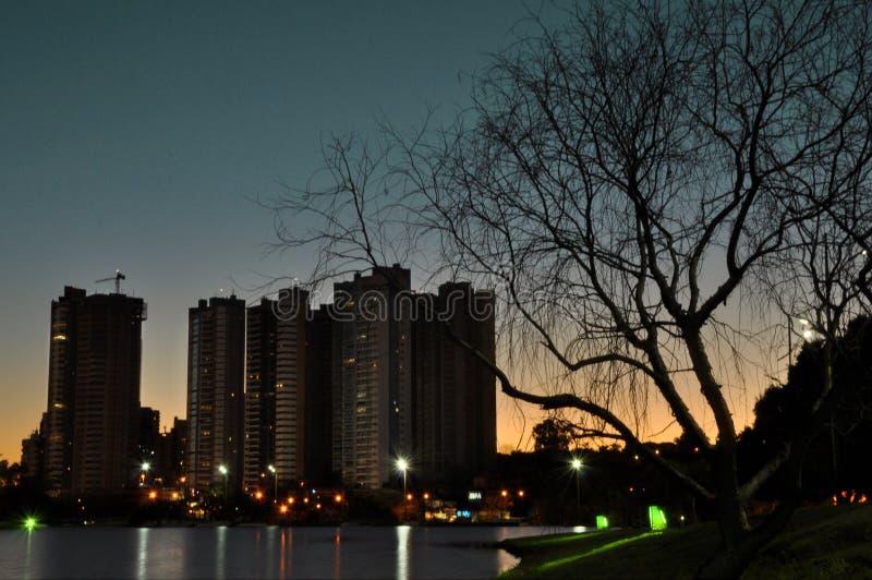Por do sol atrás das construções, água que reflete as luzes e o silhoue bonito foto de stock royalty free