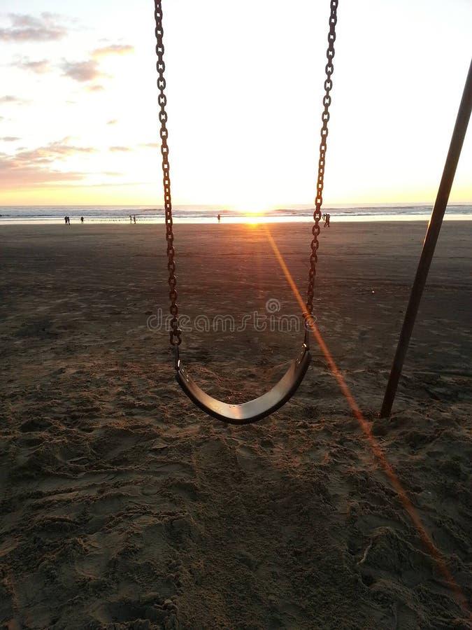 Por do sol através do balanço na praia de Pismo foto de stock