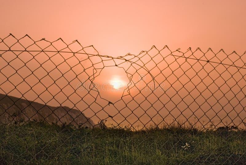 Por do sol através de uma cerca de fio quebrada. fotos de stock royalty free