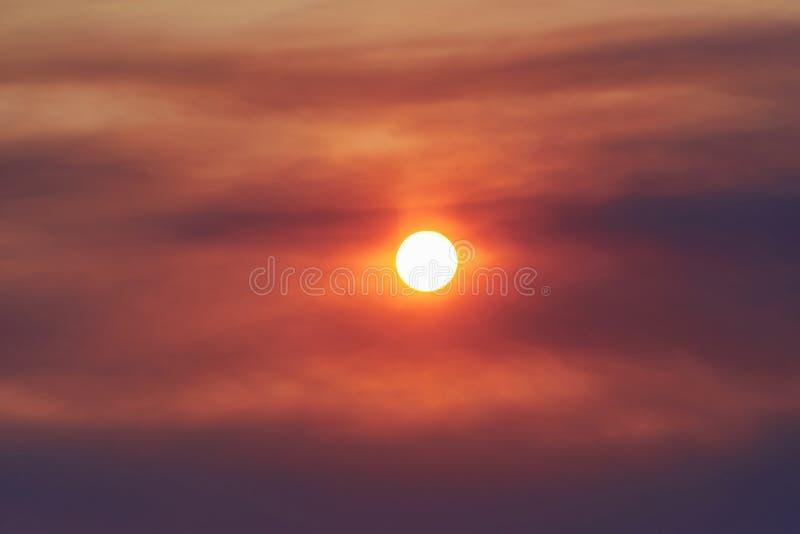 Por do sol através do fumo de um fogo fotografia de stock