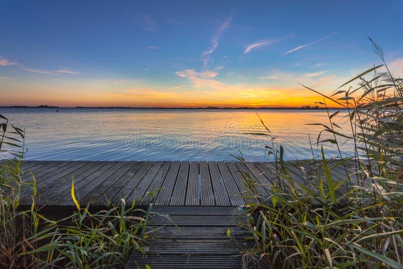 Por do sol azul e alaranjado sobre o passeio à beira mar na costa de um lago foto de stock