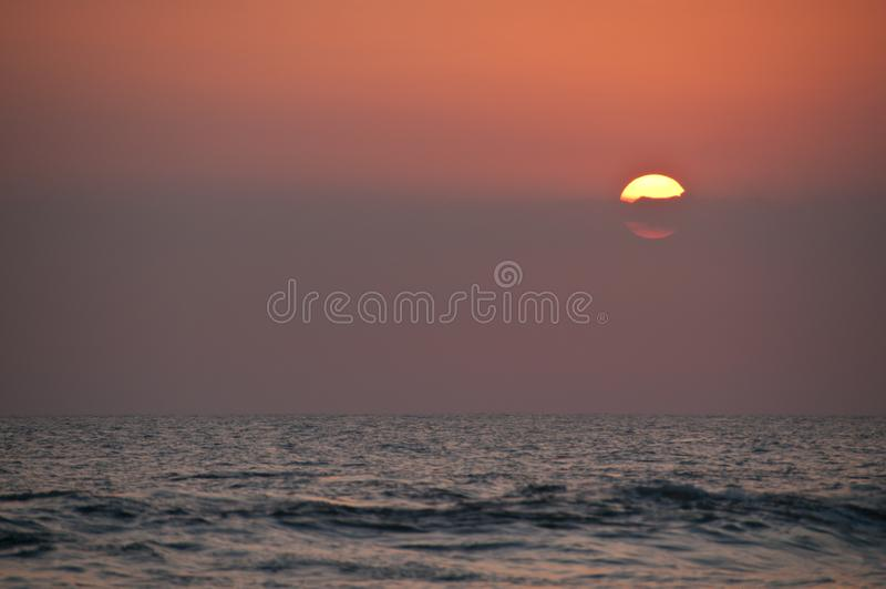 Por do sol bonito do círculo grande no mar de Bali na noite imagens de stock royalty free